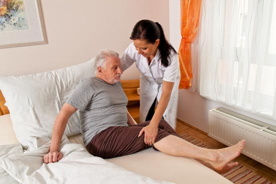 elderly man being looked after by care taker